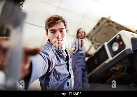 Mechanic reaching for tool below car in auto repair shop - Stock Photo