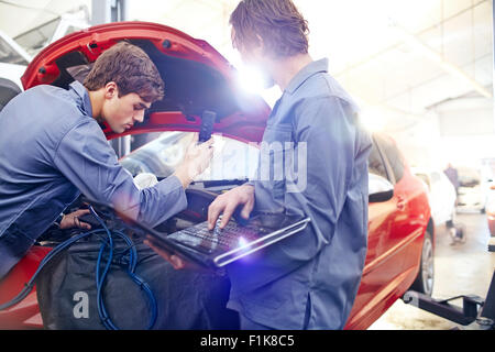 Mechanics with laptop working on car engine in auto repair shop - Stock Photo