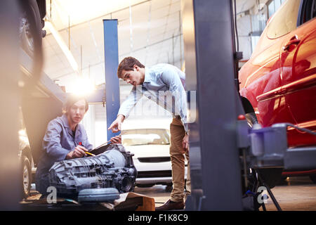 Mechanics discussing engine part in auto repair shop - Stock Photo