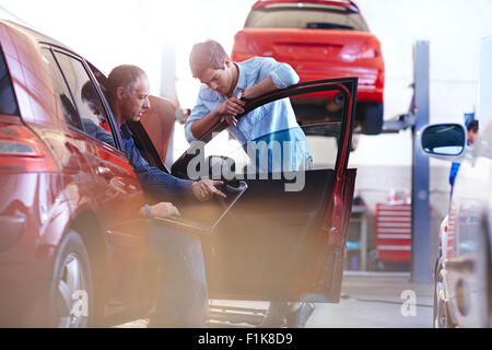 Mechanic with laptop talking to customer at car in auto repair shop - Stock Photo