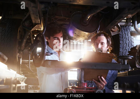 Mechanics with clipboard under car in auto repair shop - Stock Photo