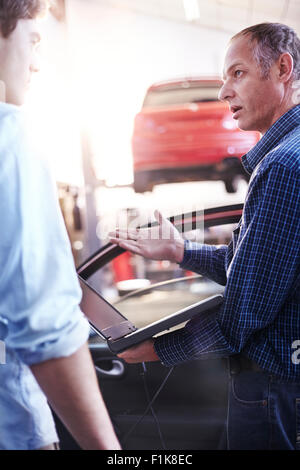 Mechanic with laptop talking to customer in auto repair shop - Stock Photo