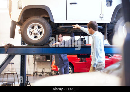 Mechanic under car talking to customer in auto repair shop - Stock Photo