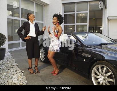 Two Young women standing by car laughing - Stock Photo