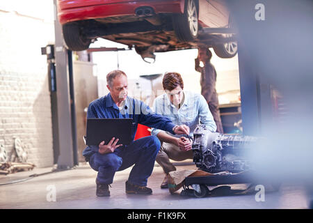 Mechanic and customer with laptop examining engine in auto repair shop - Stock Photo