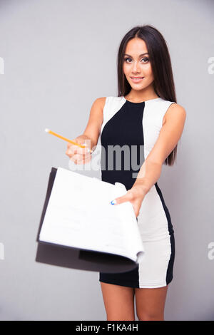 Portrait of a young woman in dress giving document to signing over gray background - Stock Photo