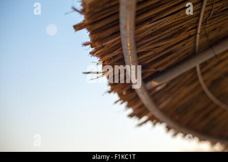 Abstract composition of cane parasol and blue sky, symbolically representing vacation on seaside. - Stock Photo