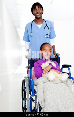 A doctor pushing a girl holding a teddy in a wheelchair - Stock Photo