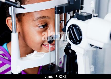 A pre-teen girl having her eye examination - Stock Photo