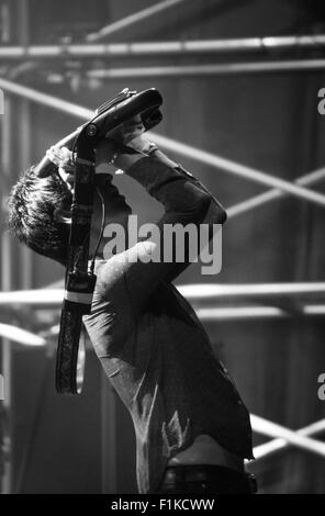 Johnny Marr at Victorious Festival 2015 holding his guitar over his head at the end of the gig. Suitable copy space. - Stock Photo