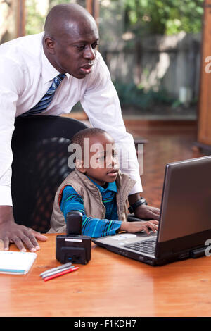 A Young African boy sits at his father's desk, playing on a leptop while his father watches over his shoulder - Stock Photo