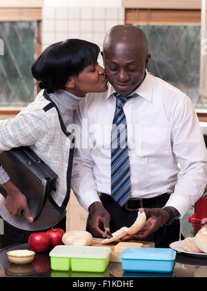 Young African man making school lunches while his wife kisses him on the cheek - Stock Photo