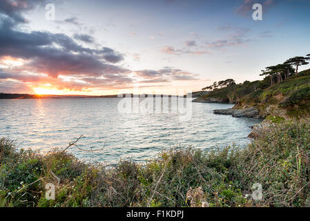 The view from St Anthony's Head in Cornwall with sunset over Falmouth in the far left and St Mawes Castle in the - Stock Photo