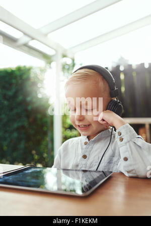 Little boy smiling in delight as he listens to music downloaded on his tablet-pc using stereo headphones while sitting - Stock Photo