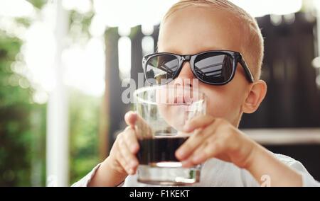 Cute hipster little boy in over sized sunglasses belonging to his mother or father sitting sipping a beverage in - Stock Photo