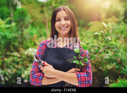 Smiling young female gardener pruning the plants standing in a lush green garden with a apir of secateurs in her - Stock Photo
