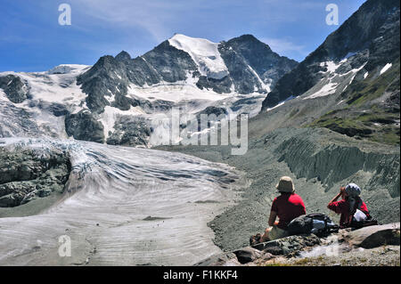 Mountain walkers / Hikers resting with view over the Moiry Glacier in the Pennine Alps, Valais / Wallis, Switzerland - Stock Photo