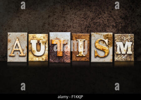 The word 'AUTISM' written in rusty metal letterpress type on a dark textured grunge background. - Stock Photo