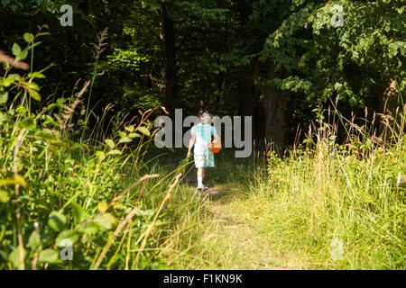 little smiling girl in green dress goes out of the forest on sunny summer day - Stock Photo
