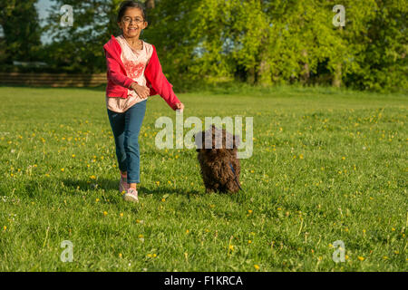 A young girl running with her Cockerpoo in a park. - Stock Photo