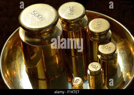 Shiny brass weighing scale weights in a brass bowl - Stock Photo