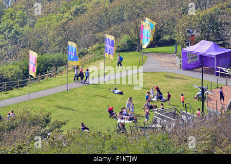 People relaxing on grass in Isle of Wight United Kingdom - Stock Photo