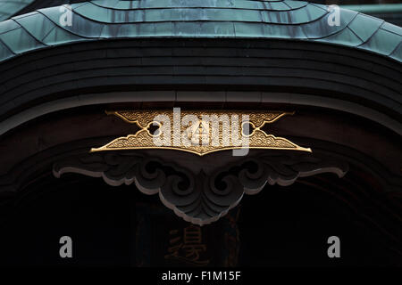 Japanese Asian temple shrine roof tile and center entrance detail in gold - Stock Photo