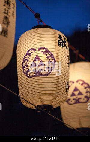Night time lit up Asian Japanese lanterns with symbols on them, depth of field. - Stock Photo