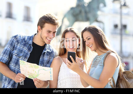 Three tourist friends consulting gps on smart phone in a touristic place with a monument in the background - Stock Photo