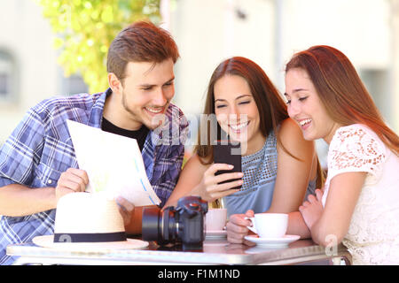 Group of three tourist friends planning vacation with a gps phone and a map in a coffee shop - Stock Photo