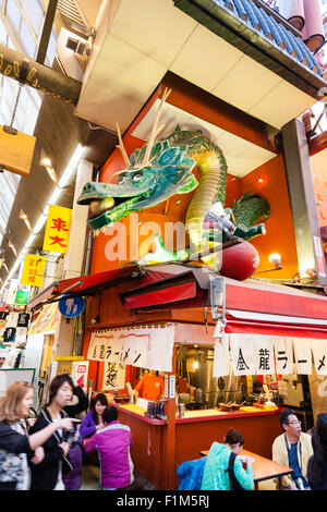 Japan, Osaka. Dotonbori, famous Kinryu Ramen noodle corner restaurant with golden dragon figure sign above. People - Stock Photo