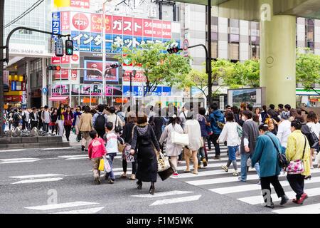 Japan, Osaka, Dotonbori. Busy scene of crowds of people on walking across a pedestrian crossing on busy main street - Stock Photo