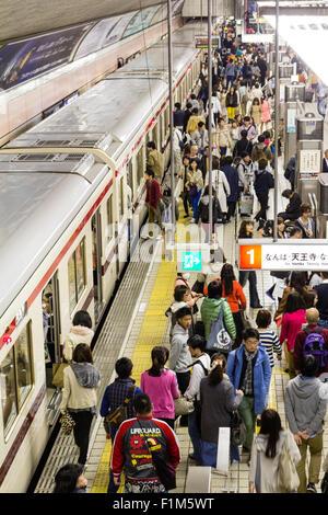 Osaka, Shinsaibashi underground metro, subway station. Overhead view of platform and passengers waiting with next - Stock Photo