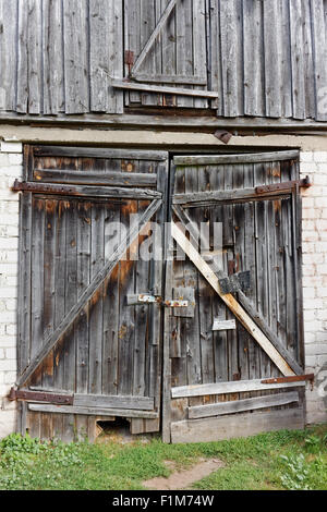 Rotten wooden gates in a brick wall of the destroyed rural shed - Stock Photo