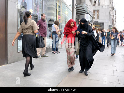 London, England, UK. Two young muslim women walking and looking at an iPhone - Stock Photo