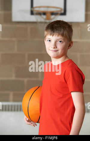 Portrait Of Boy Holding Basketball In School Gym - Stock Photo
