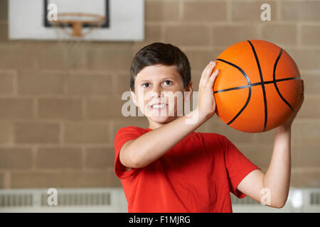 Boy Shooting During Basketball Match In School Gym - Stock Photo