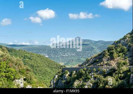 The Pech de Bugarach seen from D 9 driving down the valley from Fenouillet, Roussillon, southern France - Stock Photo