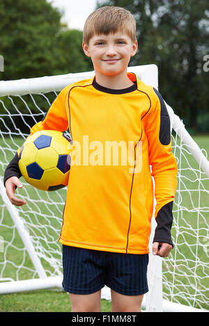 Portrait Of Goal Keeper Holding Ball On School Soccer Pitch - Stock Photo