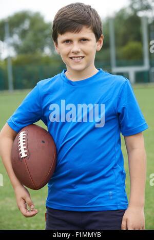 Portrait Of Boy Holding Ball On School Football Pitch - Stock Photo