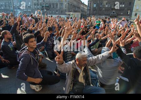 Budapest, Hungary. 4th September, 2015. Sept. 4, 2015 - Refugees sit on the ground and raise their hands in a peace - Stock Photo