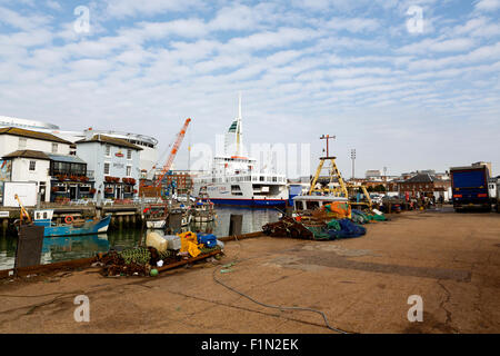 Camber Docks in old Portsmouth. Fishing equipment on the jetty in foreground with boats and ferry behind - Stock Photo