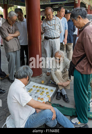 Elderly men watch others playing Chinese checkers at a park near the Temple of Heaven, Beijing - Stock Photo