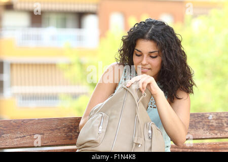 Woman searching something in her hand bag sitting in a bench of an urban park - Stock Photo