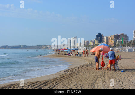 Looking along the beach at San Juan Playa towards  Alicante city, with a group of elderly men in the foreground. - Stock Photo