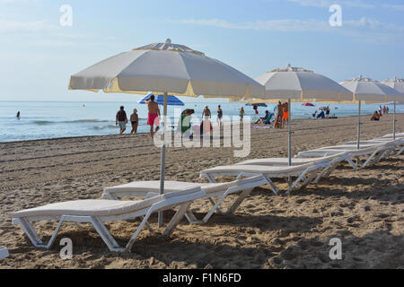 Sunbeds and parasols lined up on the beach in San Juan Playa, Alicante, with people arriving at the beach in the - Stock Photo