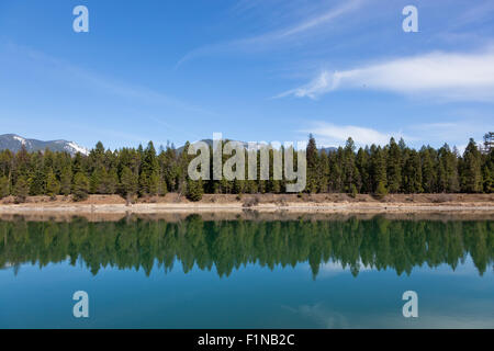 Looking across the calm waters of Trout Creek to a shoreline of fir trees and distant mountains in Montana. - Stock Photo