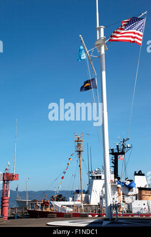 A coast guard ship docked and a mast with flags at the maritime museum in Astoria Oregon. - Stock Photo