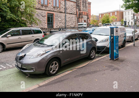 Nissan Leaf electric car charging at an on-street charging station. - Stock Photo
