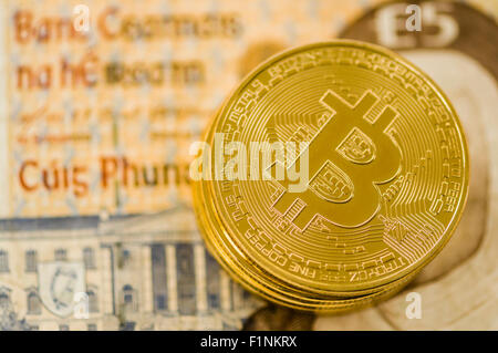 Bitcoins on an old Irish punt banknote - Stock Photo